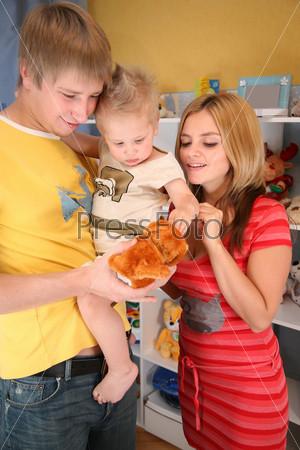 Отец держит маленького сына на руках, мама стоит рядом