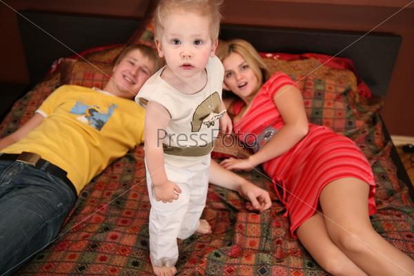 Мама и папа лежат на кровати, между ними стоит маленький сын