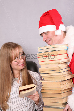 Дед Мороз с большой стопкой книг и светловолосая девушка в очках