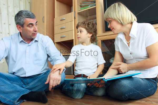 man, woman and little boy reading book