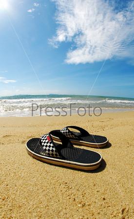 Мужские сланцы на пляже у воды