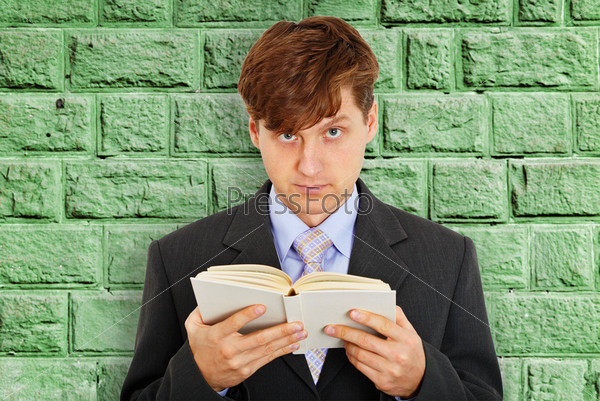 Молодой человек с книгой в руках у