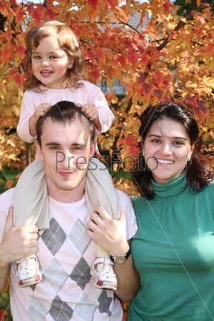 Молодой папа с маленькой дочкой на плечах, рядом стоит мама