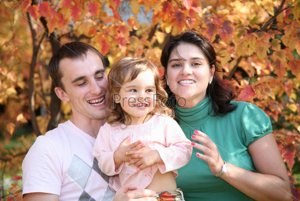 Счастливая семья: мама, папа и маленькая дочка гуляют по осеннему парку