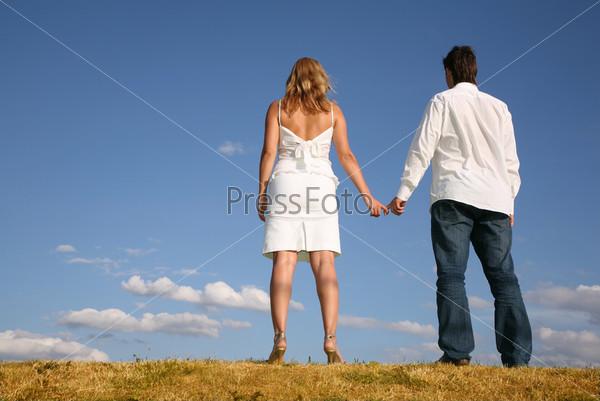 Мужчина и женщина стоят на возвышенности и держатся за руки