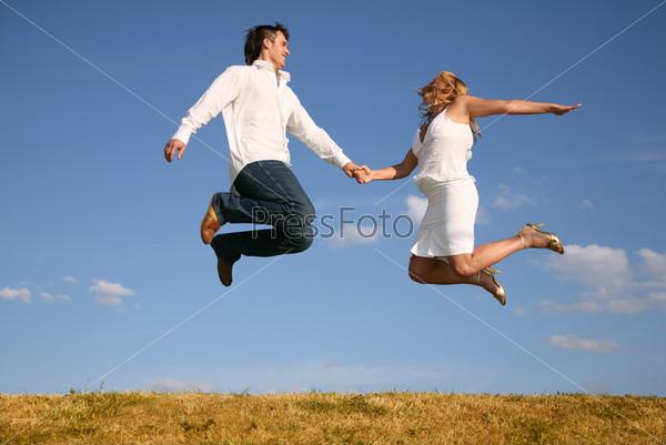 Молодые парень и девушка в прыжке на фоне неба