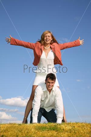 Молодой парень стоит на четвереньках, над ним, раскинув руки, стоит девушка