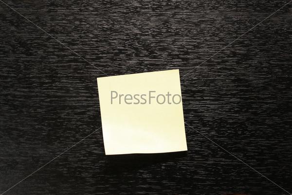 Желтый стикер бумаги на черном фоне
