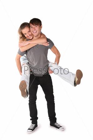 Молодая девушка обнимает парня сзади, парень держит ее ноги