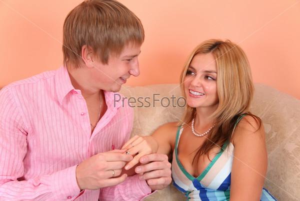 Молодой человек надевает кольцо на палец к девушке