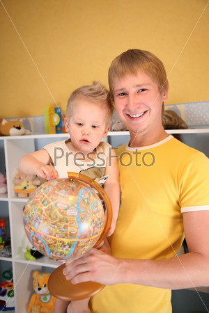 Отец и ребенок в игровой комнате с глобусом