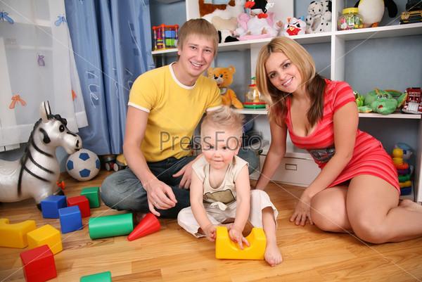 Отец и мать с ребенком в игровой комнате