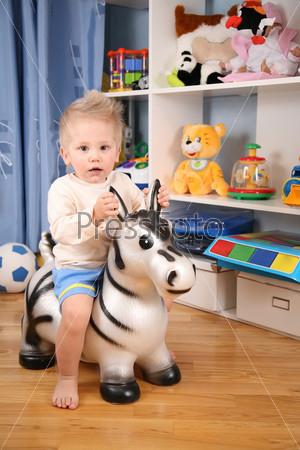 Мальчик в игровой комнате на зебре