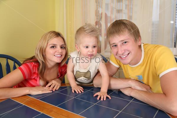 Родители с ребенком сидят за столом в комнате
