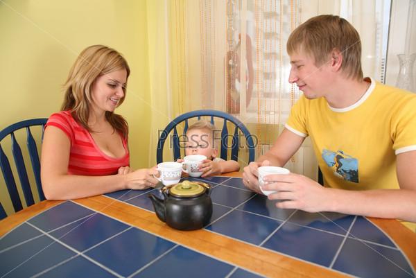 Родители с ребенком сидят за столом и пьют чай