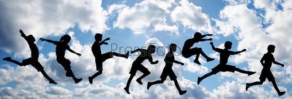 Силуэты прыгающих детей на фоне облаков