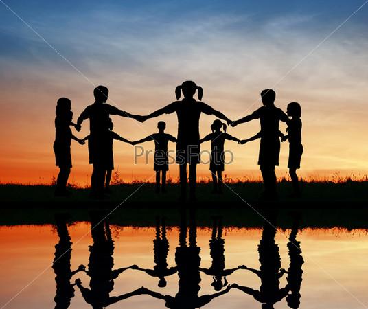 Дети стоят в кругу на закате