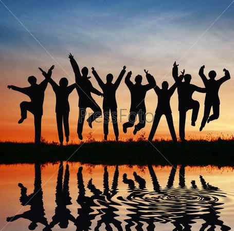 Счастливая команда в прыжке на закате