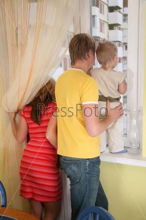 Родители с ребенком смотрят в окно
