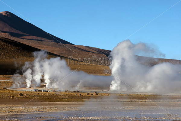Geyser field with volcano in background, Chile