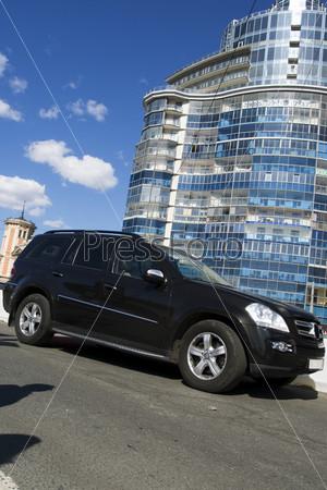 Черный автомобиль на фоне современного здания