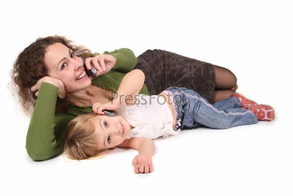 Мать и дочь лежат и разговаривают по мобильным телефонам на белом