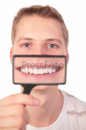 Молодой парень с улыбкой, увеличенной через лупу