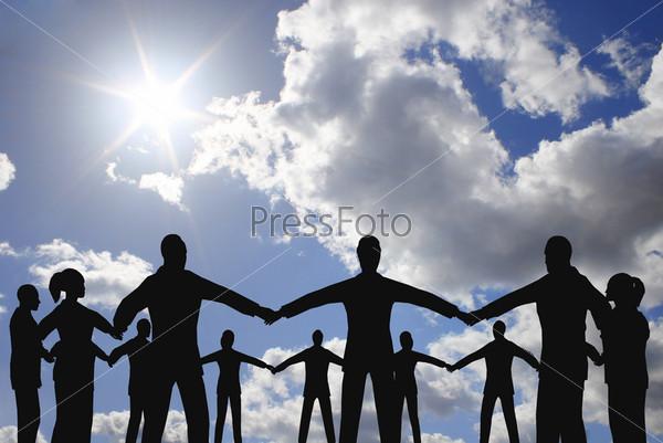 Силуэты людей, которые держатся за руки, образуя круг