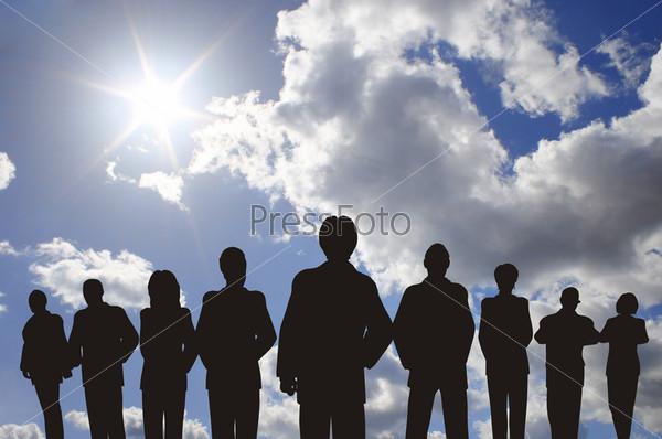 Силуэт бизнес-команды на фоне голубого неба
