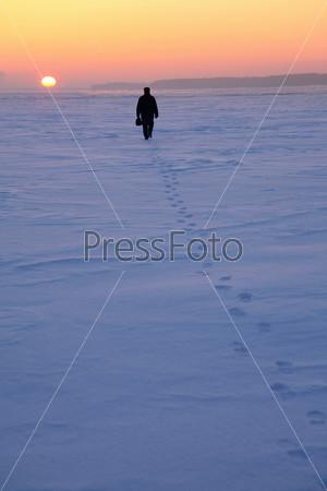 Человек идет по снежному полю