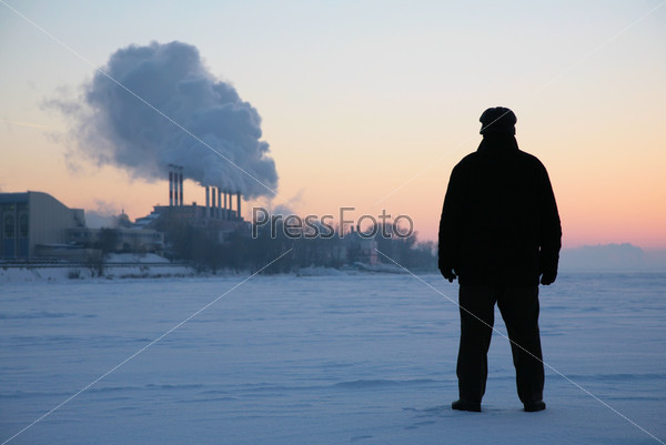 Человек стоит на замерзшей реке вблизи дымящих труб