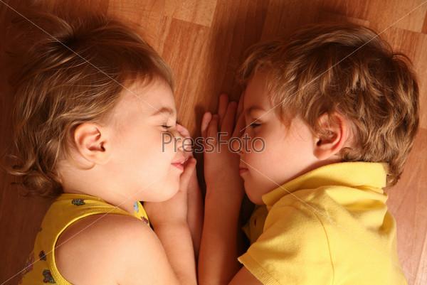 Два маленьких ребенка спят на полу лицом к лицу