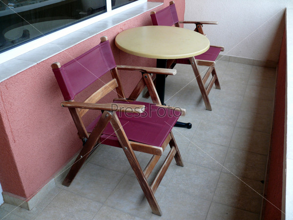 Стулья и столик на балконе.