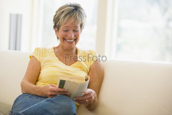 Женщина в гостиной читает книгу
