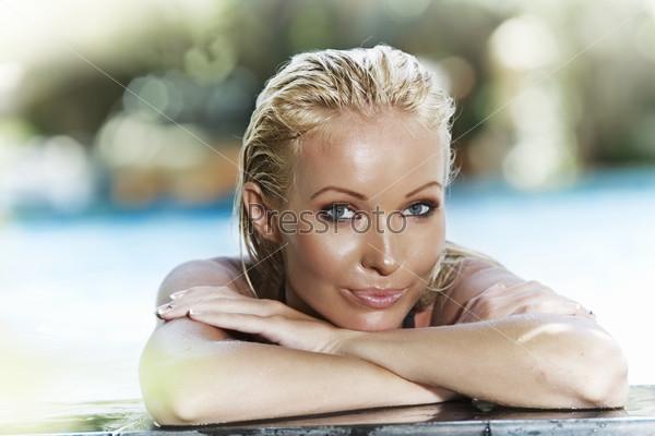 Портрет красивой блондинки, отдыхающей в бассейне