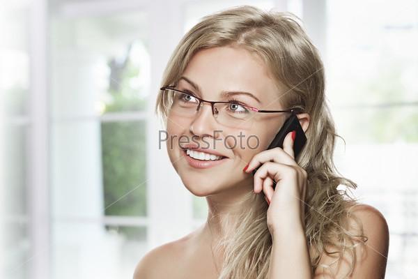 Красивая блондинка в очках разговаривает по телефону