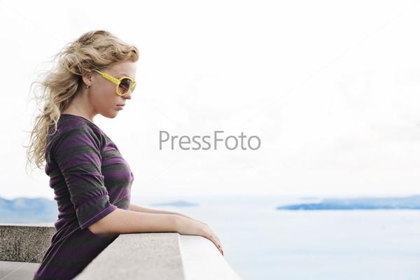 Симпатичная девушка на террасе на фоне  моря
