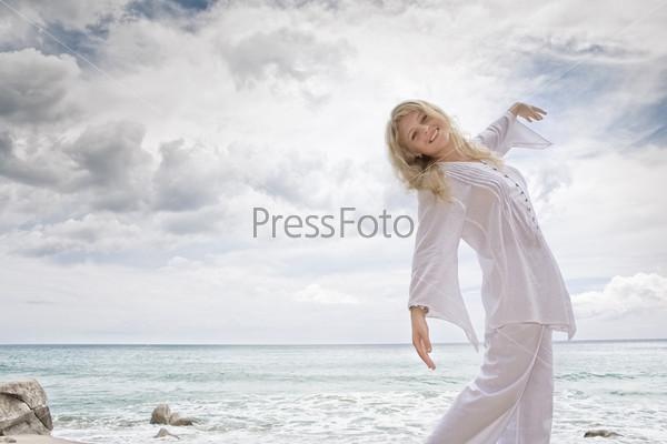 Портрет красивой блондинки в белом на берегу моря