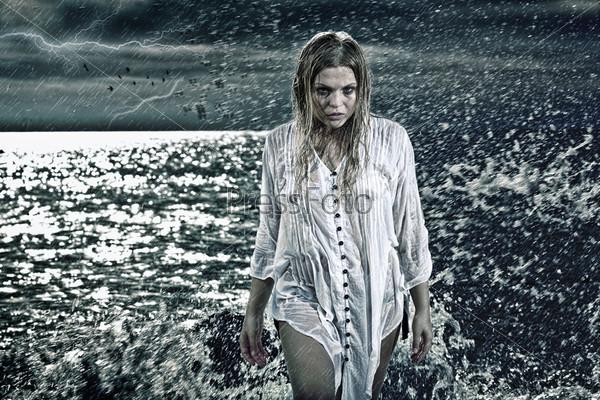 Портрет красивой блондинки на море в непогоду