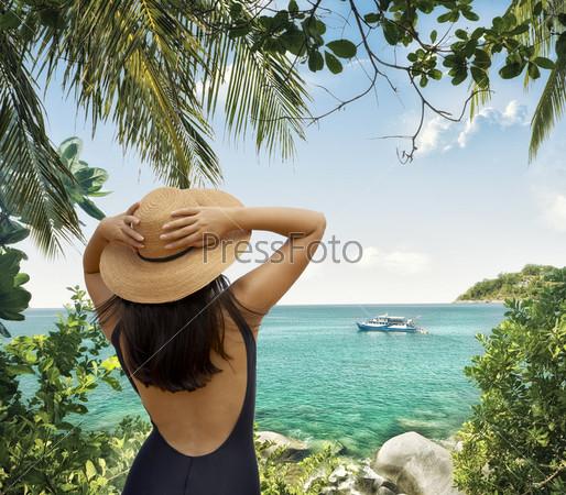Стройная женщина в шляпе на берегу моря