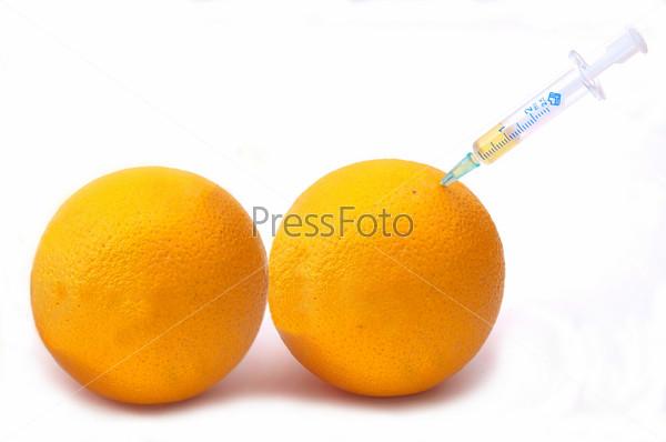 Апельсины и медицинский шприц на белом фоне