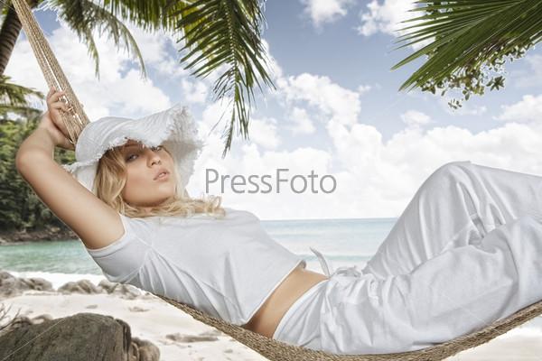 Девушка в гамаке на фоне пальм и океана