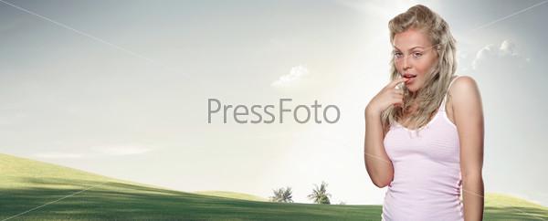 Молодая женщина на фоне зеленого луга