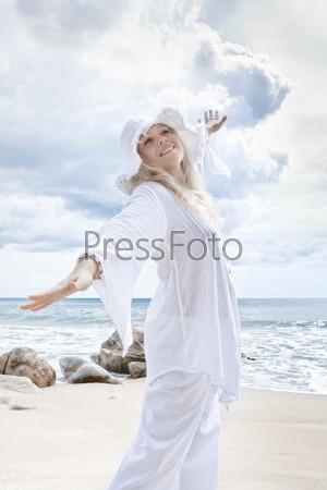 Молодая женщина в шляпе на фоне океана