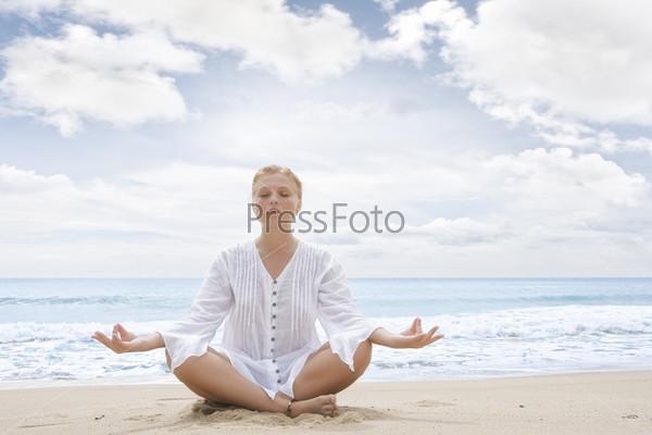 Молодая женщина медитирует на побережье