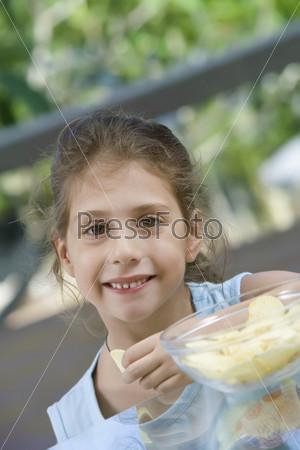 Девочка ест чипсы