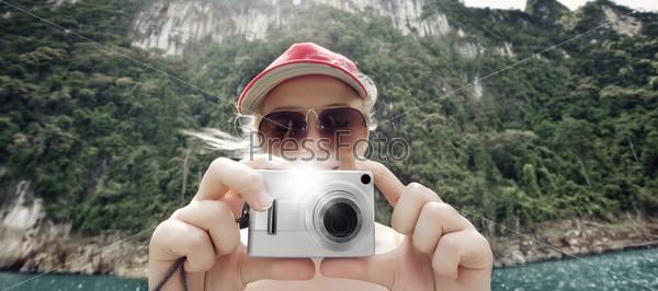 Молодая женщина-туристка с фотоаппаратом на отдыхе