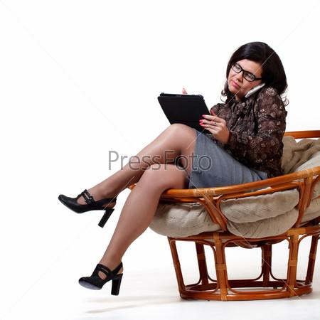 Деловая женщина сидит в мягком кресле с ноутбуком и говорит по телефону