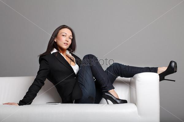Молодая девушка, сидящая на белом диване