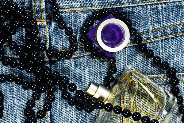 perfume and necklace on blue jeans